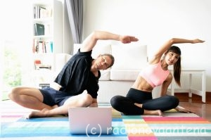 Man and woman in sports wear doing workout at home. Couple exercising together with watching laptop.